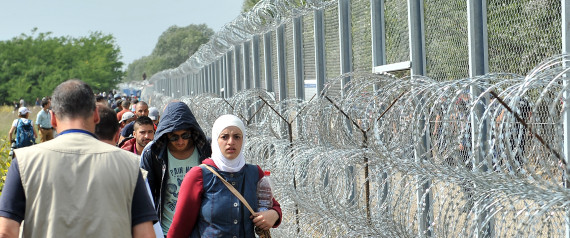 "Migrants and refugees walk near razor-wire along a 3-meter-high fence at the official border crossing between Serbia and Hungary, near the northern Serbian town of Horgos on September 15, 2015. Hungary effectively sealed its border with Serbia on September 15 to stem the massive influx of refugees as Germany slammed the ""disgraceful"" refusal of other EU countries to accept more migrants after 22 died in yet another shipwreck. AFP PHOTO / ELVIS BARUKCIC"
